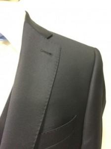 Het donkerblauw pak uit de verhuur is afgewerkt met een mooi stiksel op de kraag